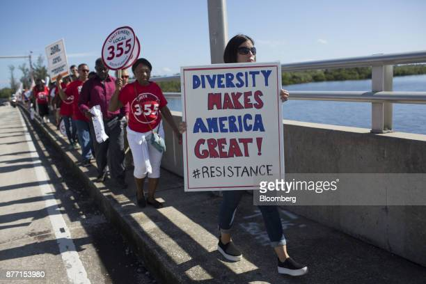 Demonstrators hold signs during a protest ahead of the arrival of US President Donald Trump at MaraLago in West Palm Beach Florida US on Tuesday Nov...