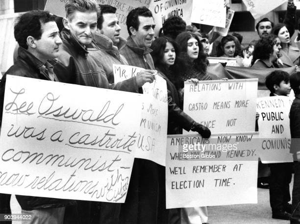 Demonstrators hold signs during a protest held by Cuban exiles living in New England outside the John F Kennedy Federal Building in Boston on April...