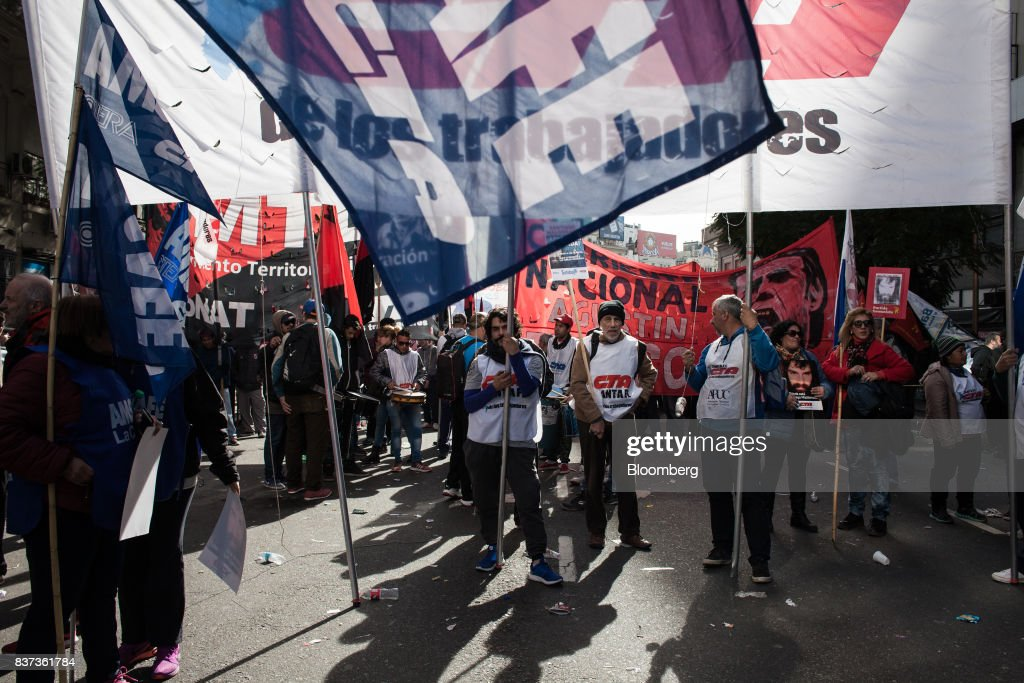 Demonstrators hold signs during a protest in Buenos Aires, Argentina, on Tuesday, Aug. 22, 2017. Union groups protested Argentinean President Mauricio Marcri's economic policies. Photographer: Erica Canepa/Bloomberg via Getty Images