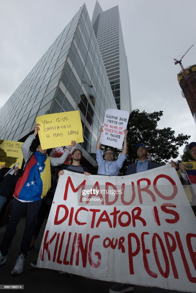 Demonstrators hold signs during a protest outside of the Goldman Sachs Group Inc. headquarters in New York, U.S., on Tuesday, May 30, 2017. Goldman faces a probe by Venezuela's opposition leaders after buying bonds issued in 2014 by the state oil company, a purchase some lawmakers said bolsters PresidentNicolas Maduroas he grapples with accusations ofhuman-rights violations. Photographer: Alexander F. Yuan/Bloomberg via Getty Images