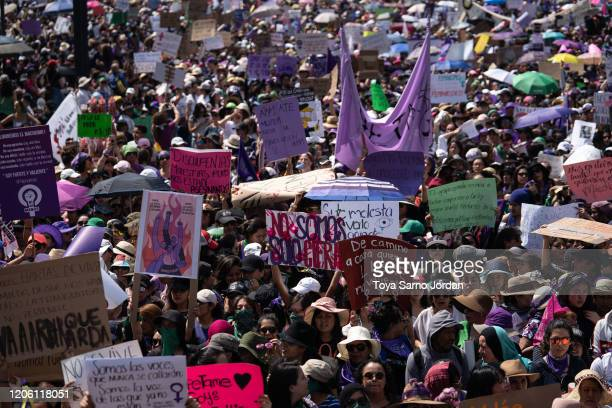Demonstrators hold signs during a rally on International Women's Day on March 8 2020 in Mexico City Mexico
