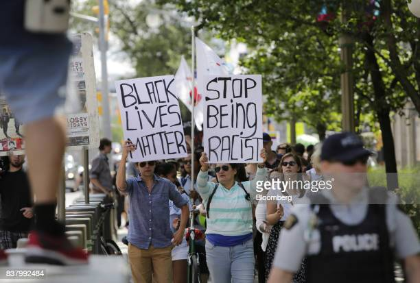 Demonstrators hold signs during an antiracism rally in front of the US Embassy in Ottawa Ontario Canada on Aug 23 2017 The peaceful gathering was...