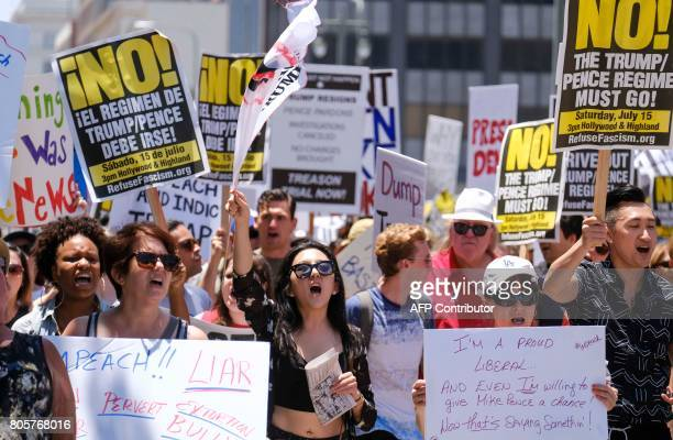 Demonstrators hold signs during the Impeachment March to call for Congress to start impeachment hearings against US President Donald Trump in Los...