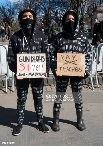 Demonstrators hold signs during the March For Our Lives on March 24 2018 in New York City Thousands of people across the country marched in support...