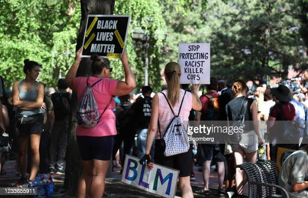Demonstrators hold signs following the sentencing of former Minneapolis police office Derek Chauvin outside Hennepin County Government Center in...