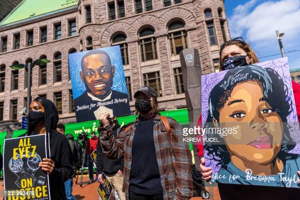 Demonstrators hold signs honouring George Floyd and other victims of racism as they gather during a protest outside Hennepin County Government Center...