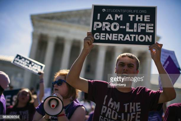 Demonstrators hold signs outside the the US Supreme Court building as the court rules on the final opinions of term in Washington DC US on Monday...