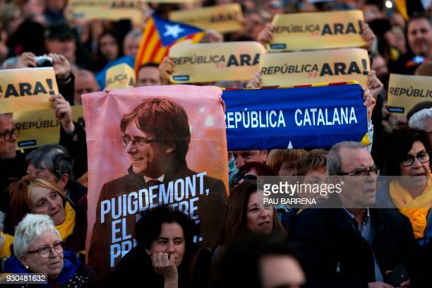 Demonstrators hold signs reading 'A republic now' along with a poster of Catalonia's deposed leader Carles Puigdemont during a protest called by the...
