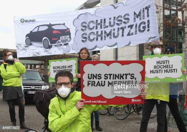 Demonstrators hold signs reading 'It Stinks to Us Ms Merkel' and 'Enough of the Filfth' in German outside of a German federal parliament or Bundestag...