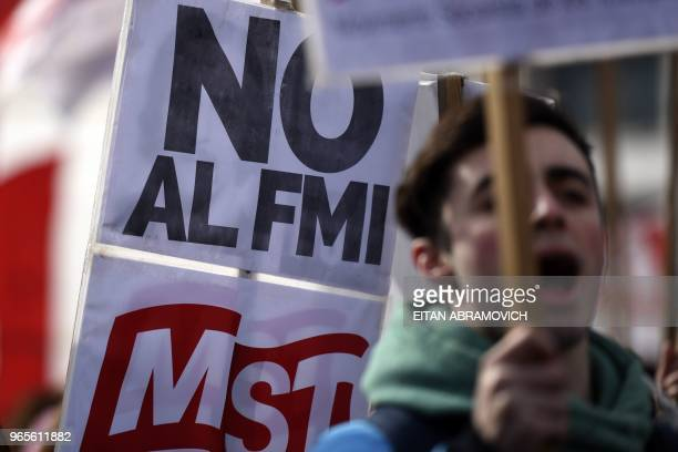 Demonstrators hold signs reading 'No to the IMF' as thousands of protesters from the provinces and from the suburbs of the Argentine capital march...