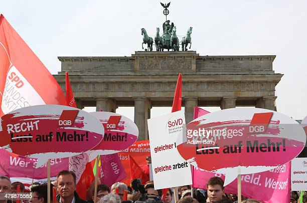 Demonstrators hold signs reading 'Not a Wish But a Right to More' in front of the Brandenburg Gate during the 'Equal Pay Day' demonstration on March...