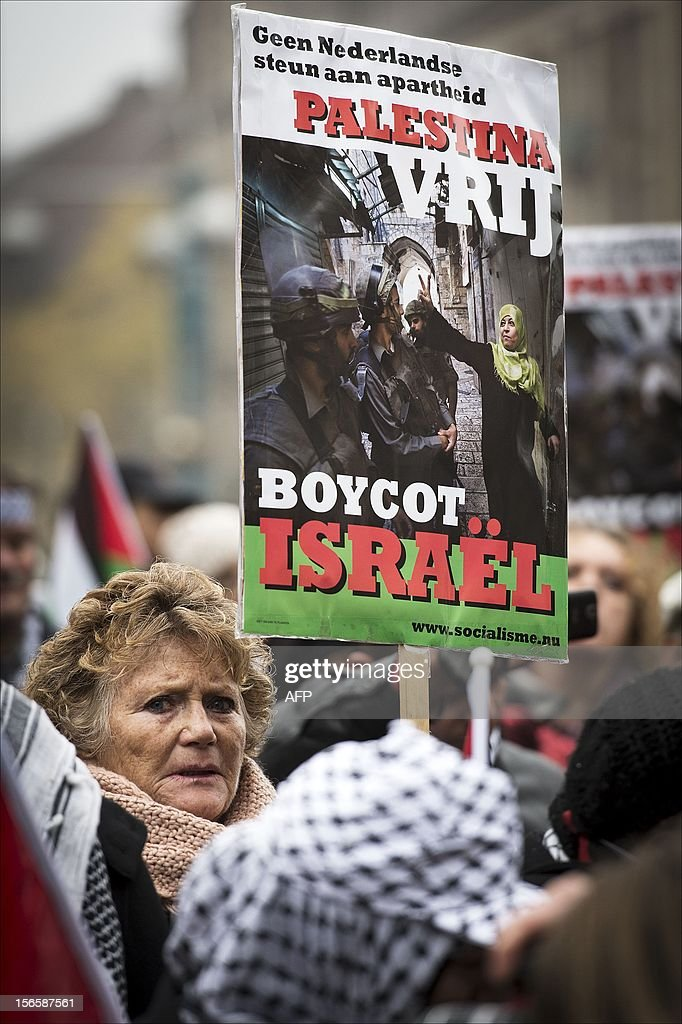 Demonstrators hold signs saying 'No Dutch support for apartheid in Palestine. Boycott Israel' during a protest in Amsterdam on November 17, 2012 against the Israeli air strikes on Palestinian targets in the Gaza Strip. AFP PHOTO / ANP / ERIK VAN ' T WOUD netherlands out