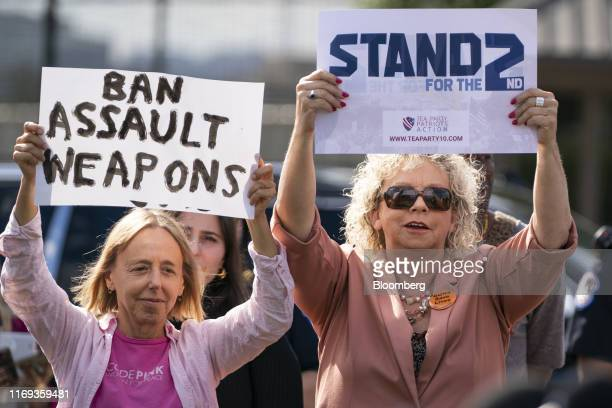 Demonstrators hold signs supporting differing political positions during a press conference on gun violence outside the U.S. Capitol in Washington,...