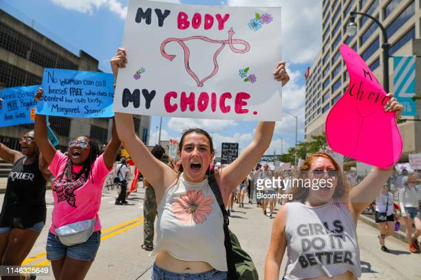 Demonstrators hold signs while marching during a protest against Georgia's heartbeat abortion bill in Atlanta Georgia US on Saturday May 25 2019...