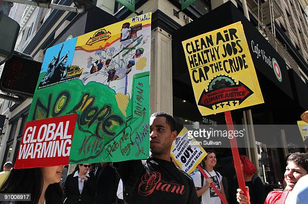 Demonstrators hold signs while marching in the streets as they protest the climate and energy bill that is currently before congress September 21...