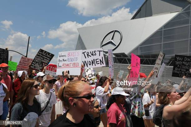 Demonstrators hold signs while marching past the MercedesBenz Stadium during a protest against Georgia's heartbeat abortion bill in Atlanta Georgia...