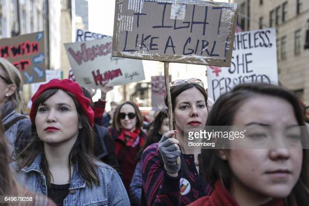 Demonstrators hold signs while protesting during the Day Without a Woman strike in New York US on Wednesday March 8 2017 Some women stayed home from...