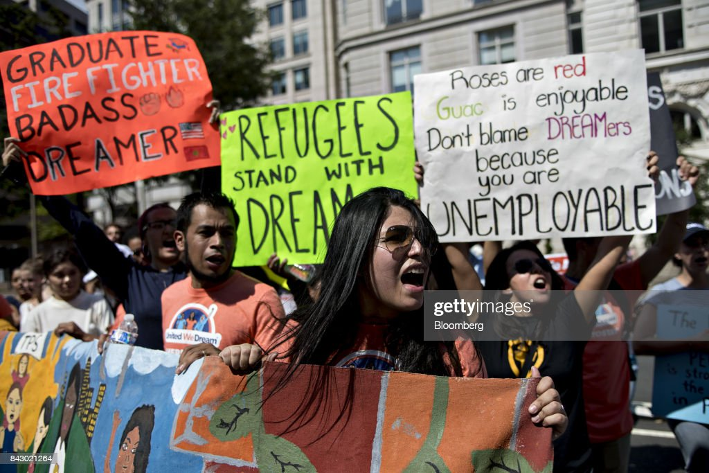 Demonstrators hold signs while protesting the end of the Deferred Action for Childhood Arrivals (DACA) program outside Trump International Hotel in Washington, D.C., U.S., on Tuesday, Sept. 5, 2017. President Donald Trump will end an Obama-era program preventing the deportation of immigrants illegally brought to the U.S. as children, U.S. Attorney Jeff Sessions said today, putting in legal limbo about 1 million people who consider themselves Americans. Photographer: Andrew Harrer/Bloomberg via Getty Images