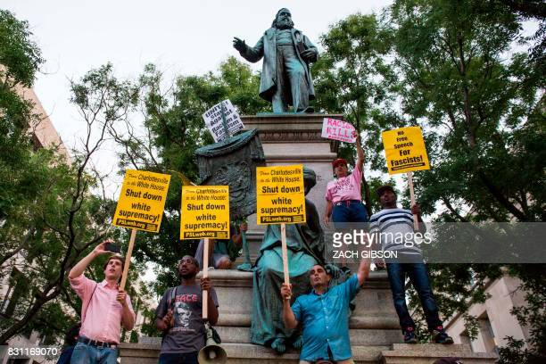 Demonstrators hold signs while standing in front of the statue of Confederate General Albert Pike on August 13 2017 in Washington DC the only member...