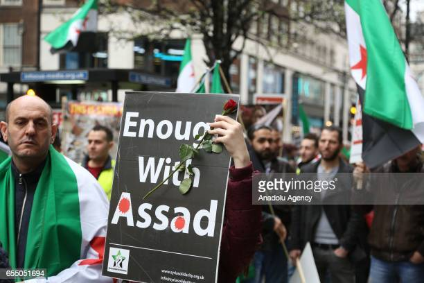 Demonstrators hold Syrian flags and banners during 6th anniversary of the Syrian Revolution march organized by a nongovernmental organization called...