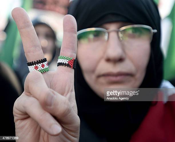 Demonstrators hold Syrian flags and shout slogans during a protest marking the third anniversary of the start of the Syrian conflict in Istanbul,...