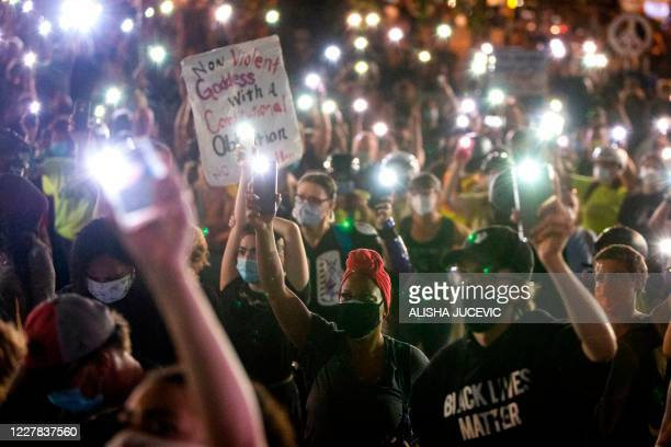 Demonstrators hold their cellphone lights in the air as they gather outside the Justice Center during a night of protest against police brutality and...