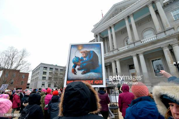Demonstrators hold their signs and cheer as they listen to speakers at a Women's March and Rally at the New Hampshire State House in Concord New...