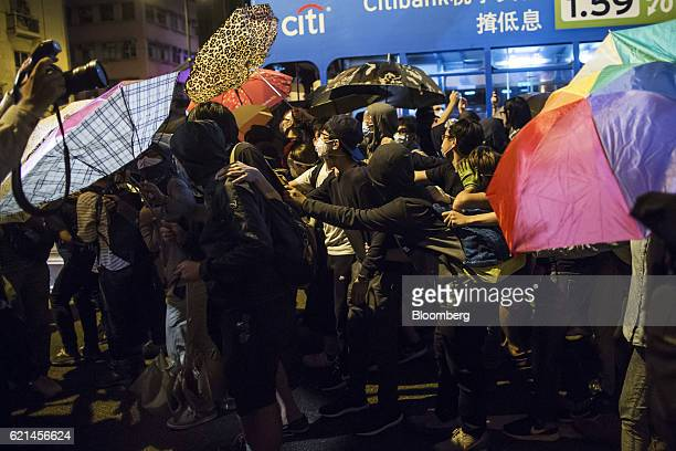 Demonstrators hold umbrellas during a protest outside the Liaison Office of the Central People's Government in Hong Kong China on Monday Nov 7 2016...
