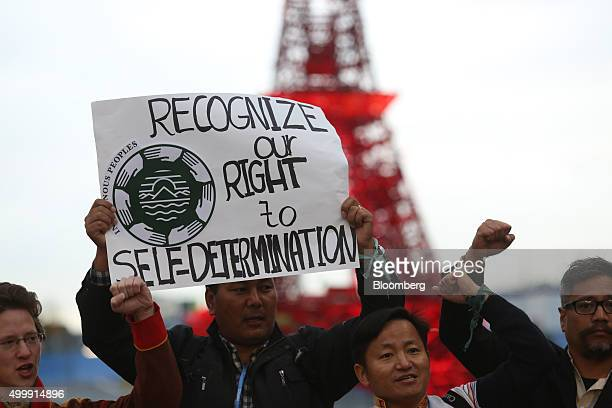 Demonstrators hold up a placard during an indigenous peoples' protest at the United Nations COP21 climate summit at Le Bourget in Paris France on...