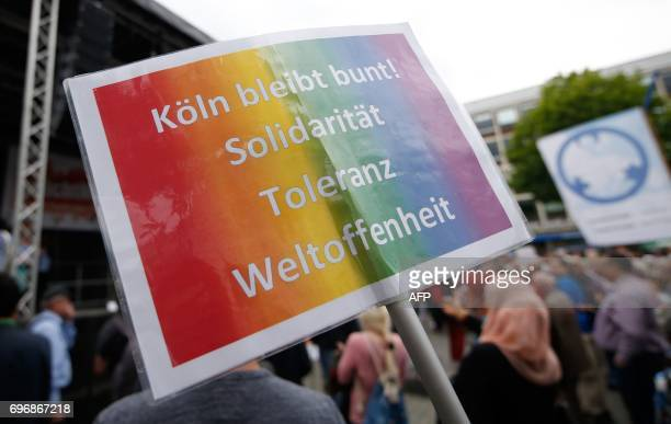 Demonstrators hold up a poster reading Cologne stays colorful Solidarity tolerance cosmopolitanism as they take part in a socalled Ramadan Peace...