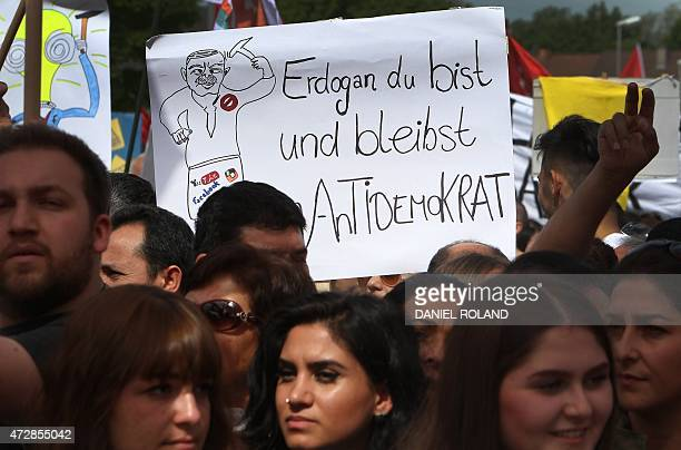 Demonstrators hold up a poster reading 'Erdogan you are and remain an antidemocrat' as they protest against Turkish President Recep Tayyip Erdogan's...
