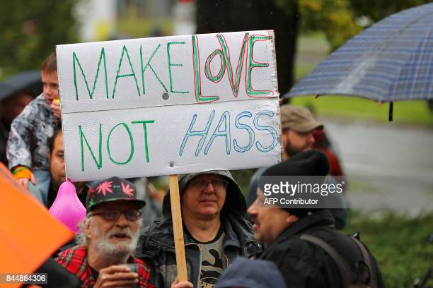 Demonstrators hold up a poster reading 'Make Love not Hate' protest against an election campaign event of Germany's antiIslam antiimmigration AfD...