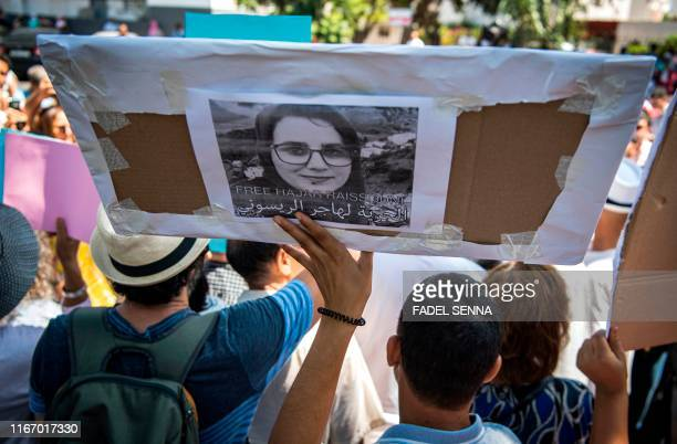 Demonstrators hold up a sign showing the portrait of Hajar Raissouni a Morrocan journalist of the daily newspaper Akhbar ElYoum with a caption below...