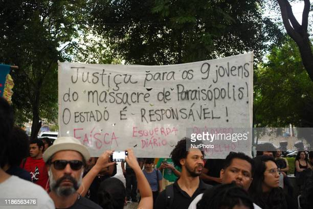 """Demonstrators hold up a sign that reads """"Justice for the nine youths of the Paraisopolis massacre. The state is responsible."""" during a..."""