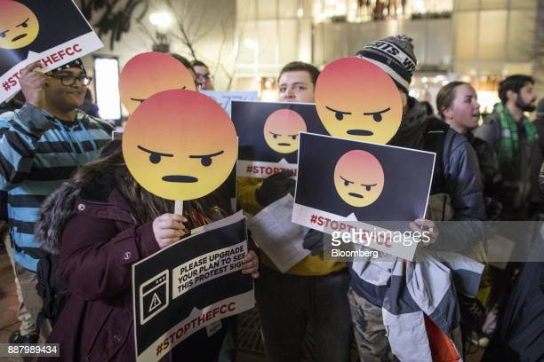 Demonstrators hold up angry emoji signs during a net neutrality protest outside a Verizon Communications Inc store in Boston Massachusetts US on...