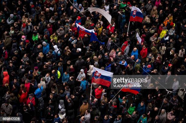 Demonstrators hold up flags of Slovakia during an anticorruption rally in Bratislava Slovakia on April 18 2017 Thousands of protesters joined a...