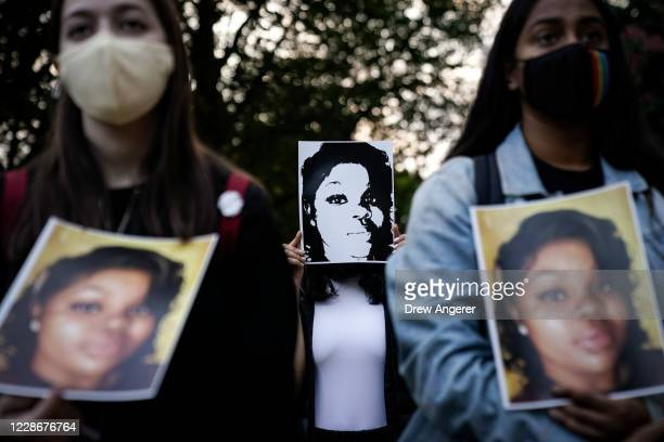 Demonstrators hold up images of Breonna Taylor as they rally in front of the US Department of Justice in protest following a Kentucky grand jury...