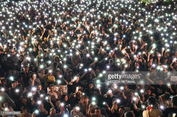 Demonstrators hold up lights from their phones during a rally organised by Hong Kong mothers in support of extradition law protesters, in Hong Kong...