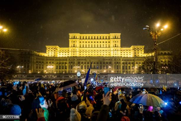 Demonstrators hold up mobile phones during an antigovernment and anticorruption protest in front of the Romanian Parliament building in Bucharest on...
