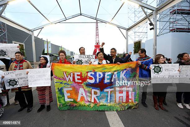 Demonstrators hold up placards and a banner during an indigenous peoples' protest at the United Nations COP21 climate summit at Le Bourget in Paris...