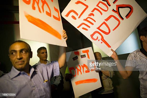 Demonstrators hold up placards as they march through the streets to protest against Israeli Finance Minister Yair Lapid's budget cuts on May 18 2013...