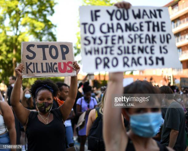 Demonstrators hold up placards during a march to the US Embassy in central London on May 31, 2020 to protest the death of George Floyd, an unarmed...