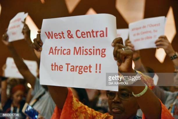 Demonstrators hold up placards during the opening of the 19th ICASA conference on December 4 2017 in Abidjan The 19th ICASA conference will take...