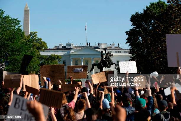TOPSHOT Demonstrators hold up placards protest outside of the White House over the death of George Floyd in Washington DC on June 1 2020 President...