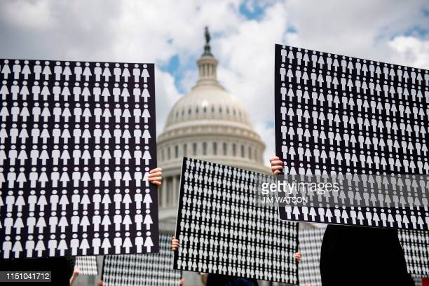 TOPSHOT Demonstrators hold up placards representing the number of the people who have died due to gun violence on Capitol Hill in Washington DC on...