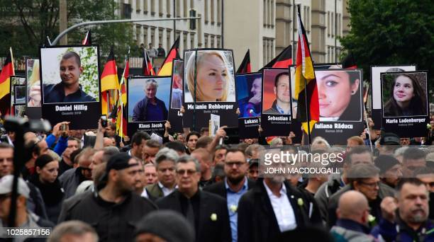 Demonstrators hold up placards showing portraits of victims of refugees during a protest organised by the far-right Alternative for Germany party, on...