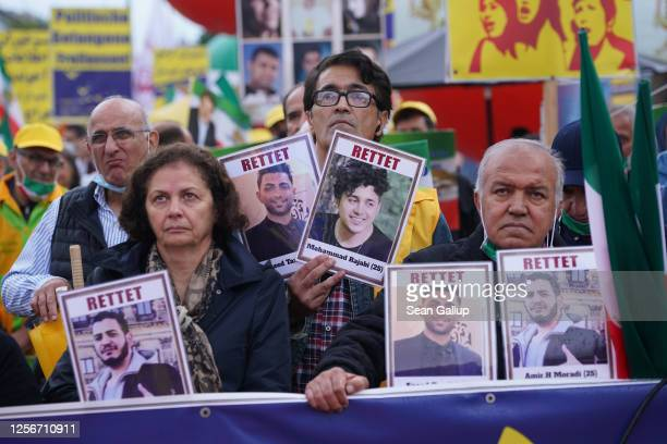 Demonstrators hold up portraits of Amirhossein Moradi Mohammad Rajabi and Saeed Tamjidi who took part in street demonstrations in Iran last year and...