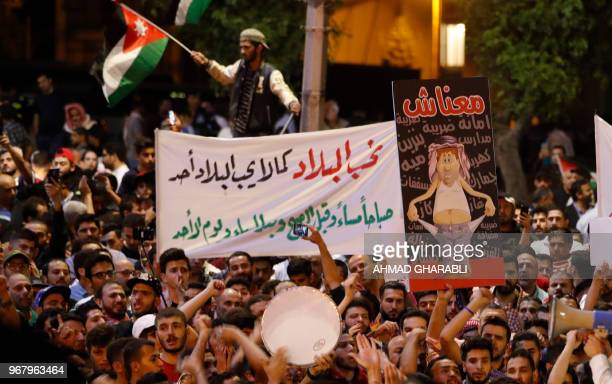 Demonstrators hold up posters in front of Jordanian policemen during a protest near the prime minister's office in Amman Jordan on June 6 2018...