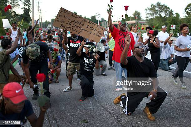 Demonstrators hold up roses while protesting the shooting death of Michael Brown make their voices heard on August 18, 2014 in Ferguson, Missouri....