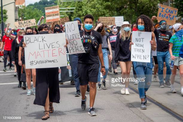 Demonstrators hold up signs during a Mass Action for Black Liberation protest and march from Washington Park to City Hall following the alleged...